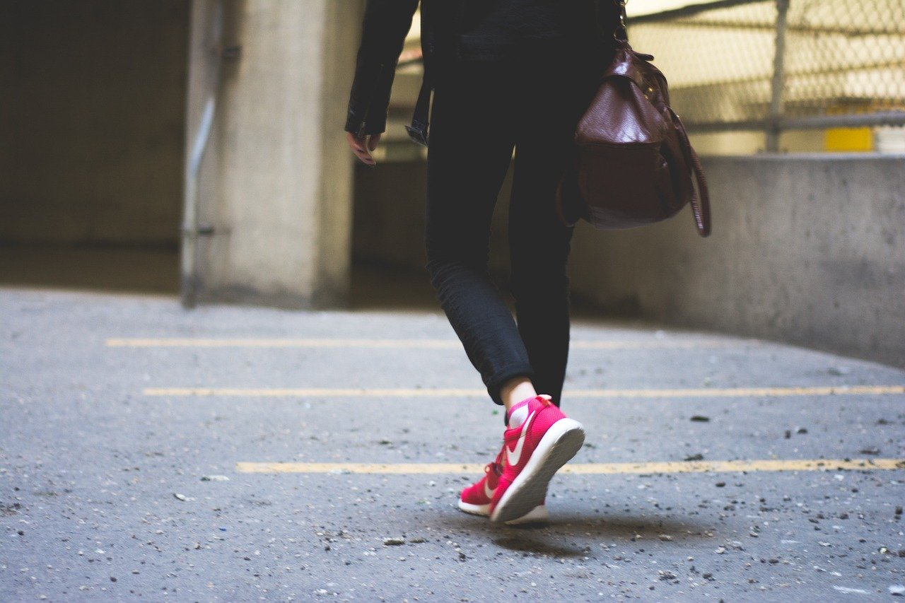 A woman in sportswear and pink Nike trainers