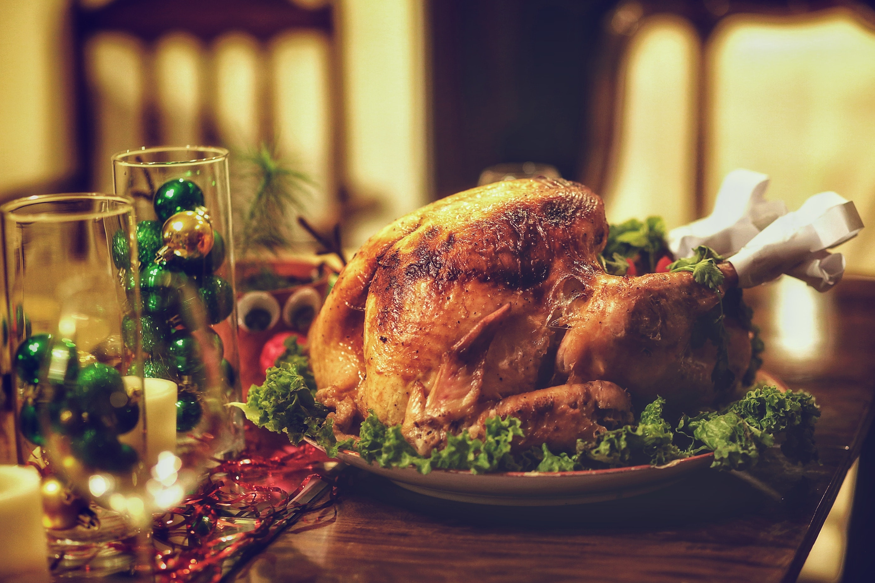 Roast chicken sat on a festively decorated table, complete with red and green decorations, candles and wine glasses