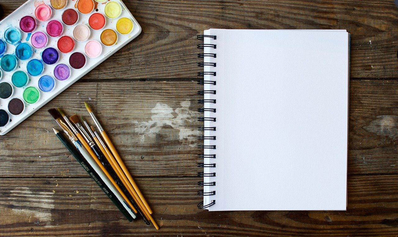 Paints, paper, pens and a notepad on a wooden table, providing an outlet for creativity
