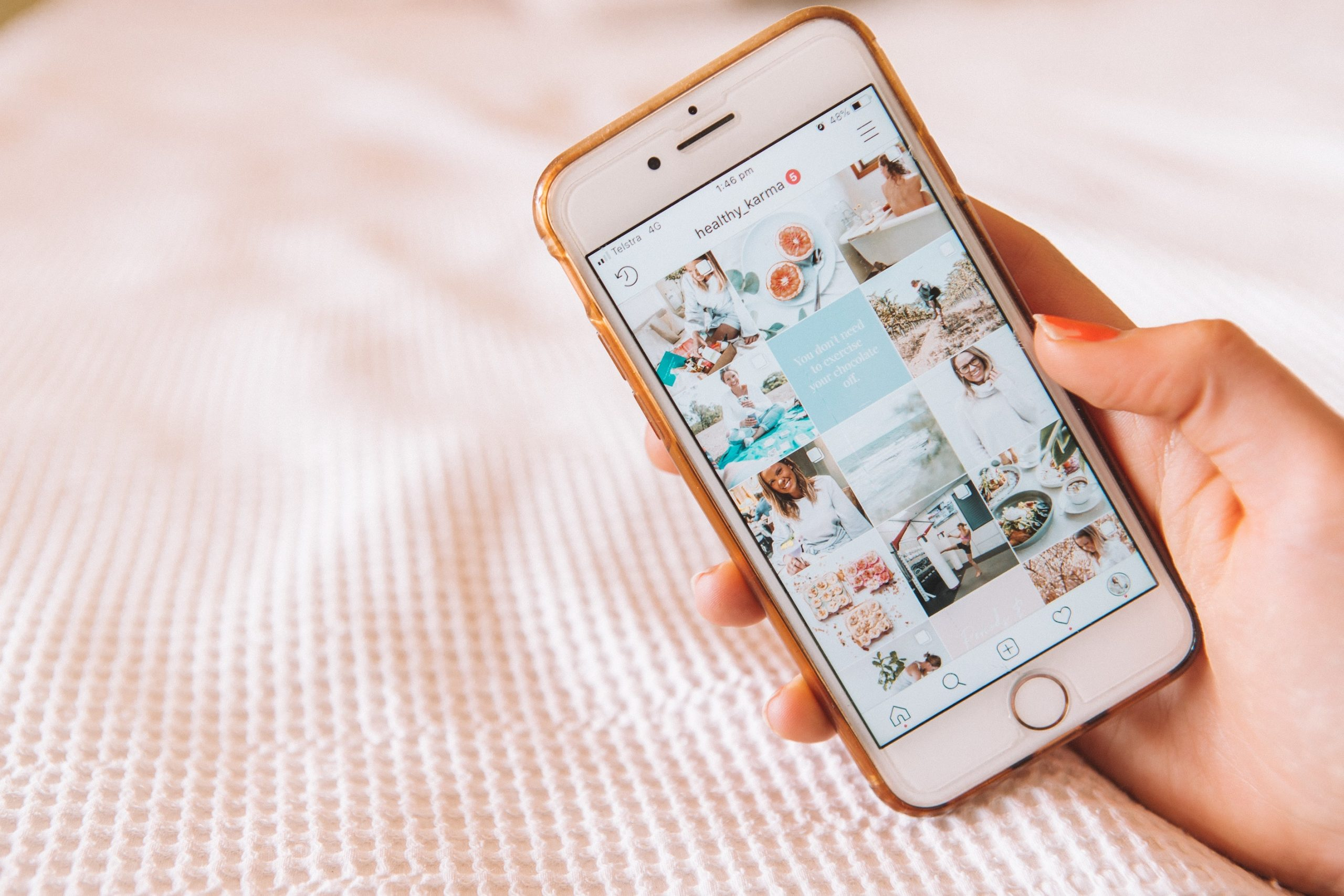 A rose gold mobile phone with the Instagram app open and a light pink bedding background